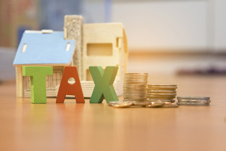 Tax sign with model house and pile of coins